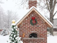 Red brick enclosed Casa 90 Pizza Oven with green wreath and red bow on front - Snow falling - small evergreen next to it