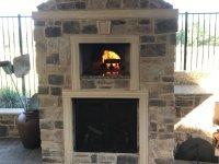 Stone enclosed Artigiano brick pizza oven with fire burning