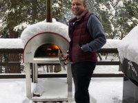 Man in front of a Bella Medio28 Wood Burning Oven In a Foot of Snow