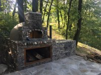 Tan Stucco and Grey Rock-Faced Pompeii Pizza Oven and Prep Counter on a Serbian Hillside in the Woods