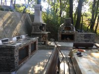 Grey stone faced outdoor kitchen with pizza oven - fireplace - prep area - picnic table