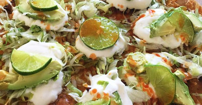 Pizza topped with pancetta-shrimp-vegetables-lettuce-lime_crema-lime_slices-avacado