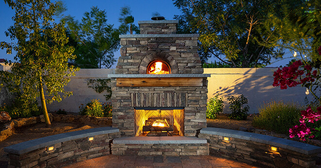 Stone enclosed Giardino70 Pizza Oven with with burning fire above fireplace box