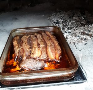Pyrex pan with bacon covered brisket in wood fired oven