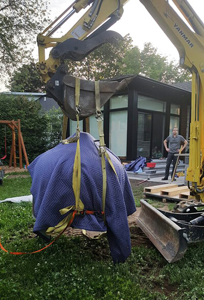 Pizza Oven wrapped in blankets hanging from a back hoe