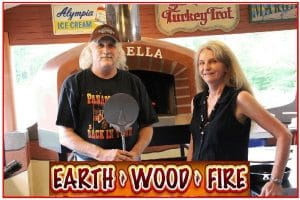 Man adn Woman in front of wood fired oven