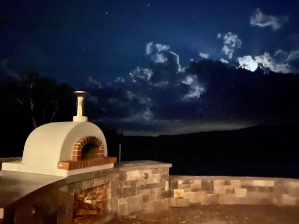 white domed Toscana oven-stone wall- night ski
