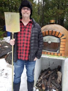 Male with Pizza Peel adn Wood Fired Oven in Snow