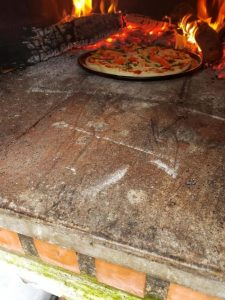 Pizza on pan in wood fire oven
