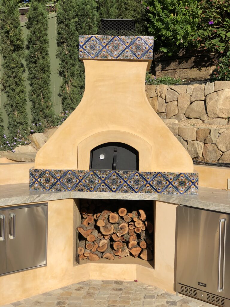 Yellow stucco pizza oven with tall chimney