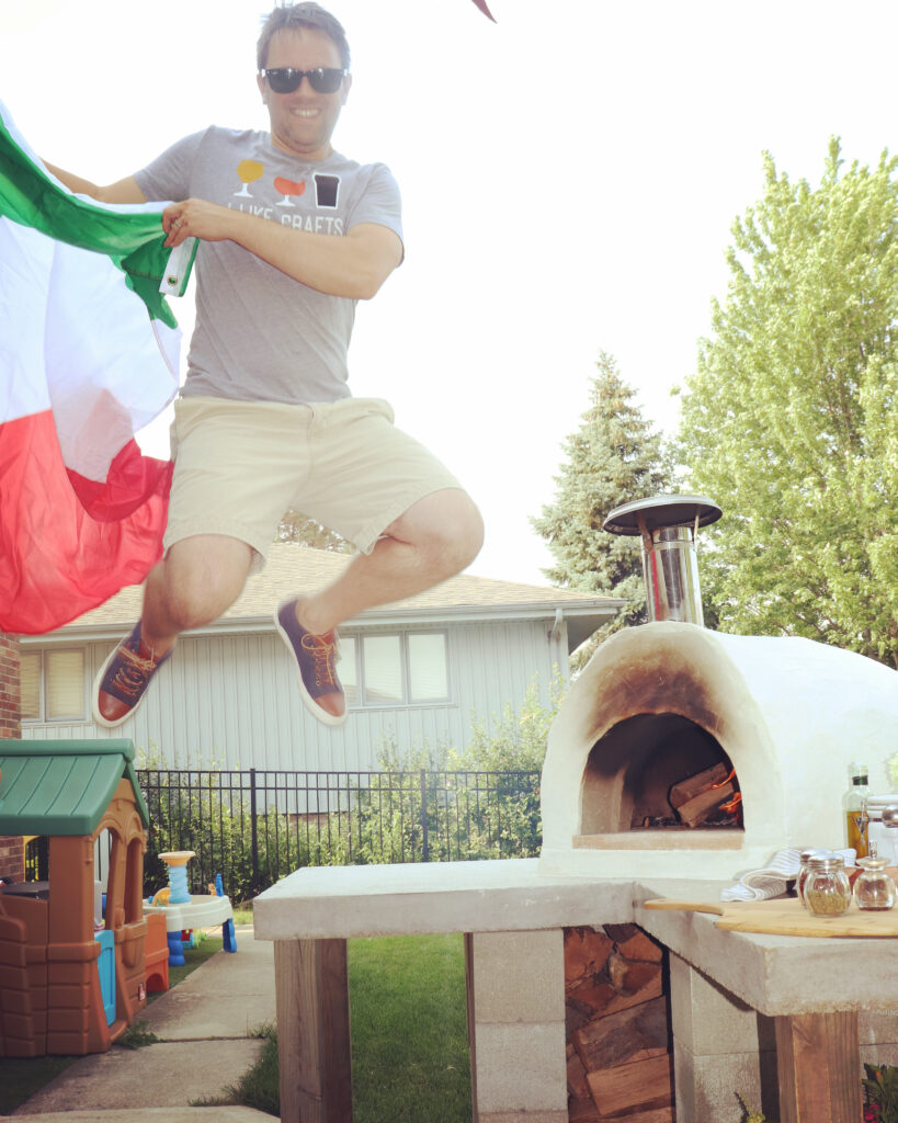 man jumping-holding italian flad-pizza oven